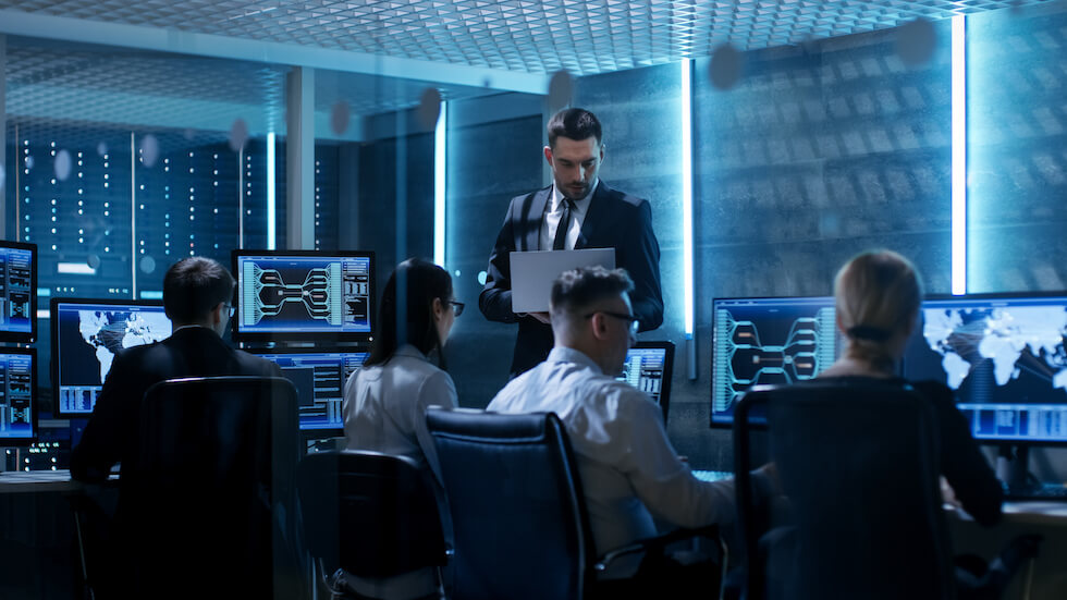 Professional IT Engineers Working in System Control Center Full of Monitors and Servers